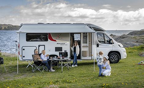 Familie utenfor campingvogna si, som står parkert ved sjøen