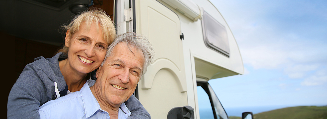 Cheerful senior couple standing by camper door