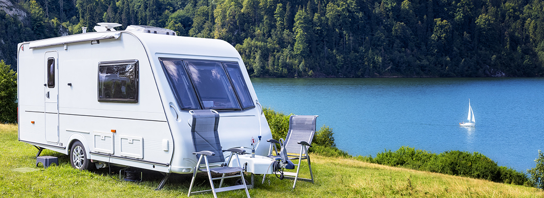Summer scene with camper trailer by the Czorsztyn lake and Tatra Mountains landscape, Poland